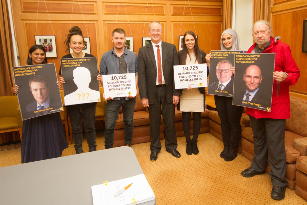 At the petition handover in May: Tenisha Kumar (AUT Human Rights), Laura O'Connell Rapira (ActionStation), James Crow (Gimme Shelter), Phil Twyford (Labour, now Minister for Housing), Jacinda Ardern (Labour, now Prime Minister), Shahd Mahmoud (AUT Human Rights) and Dr Desmond Darby (ActionStation volunteer) with images showing the OECD Ministers responsible for homelessness alongside the missing New Zealand Minister.